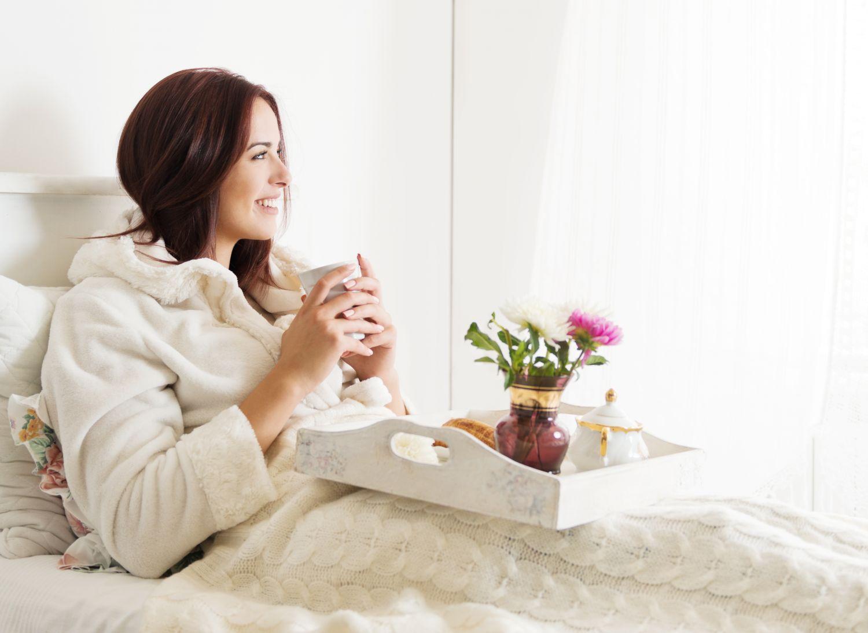 Eine Frau genießt im Bett eine Tasse Kaffee