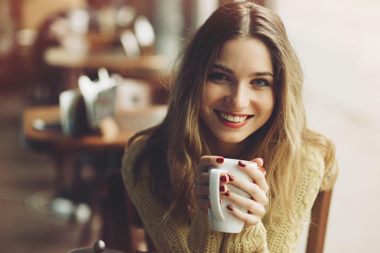 Eine Frau genießt in einem Café ihren Kaffee.