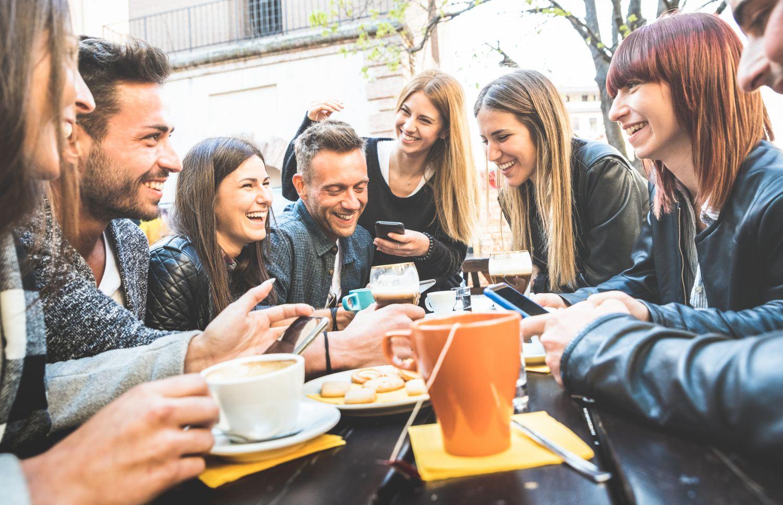 Mehrere junge Leute sitzen bei Kaffee und Gebäck zusammen. Thema: Kaffee genießen
