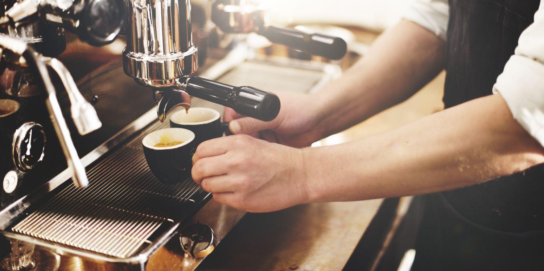 Ein Mensch holt zwei volle Espressotassen aus einer Kaffeemaschine. In einer Luxusküche gehört der Kaffeevollautomat dazu
