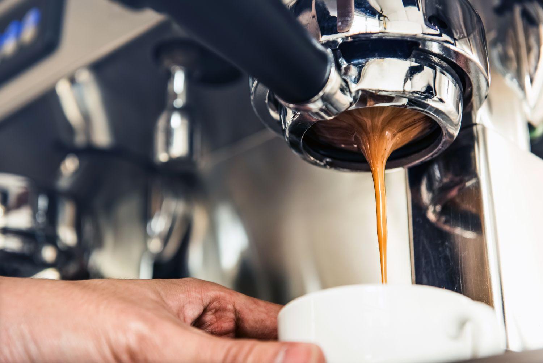 Frisch aufgebrühter Kaffee läuft aus einer Maschine in die Tasse. Thema: Espresso zubereiten