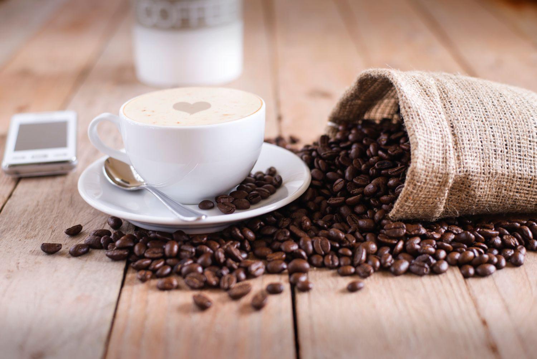 Eine dampfende Kaffeetasse steht neben einem umgekippten Sack Kaffeebohnen