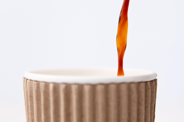 Detail: Kaffee wird in einen Pappbecher eingegossen