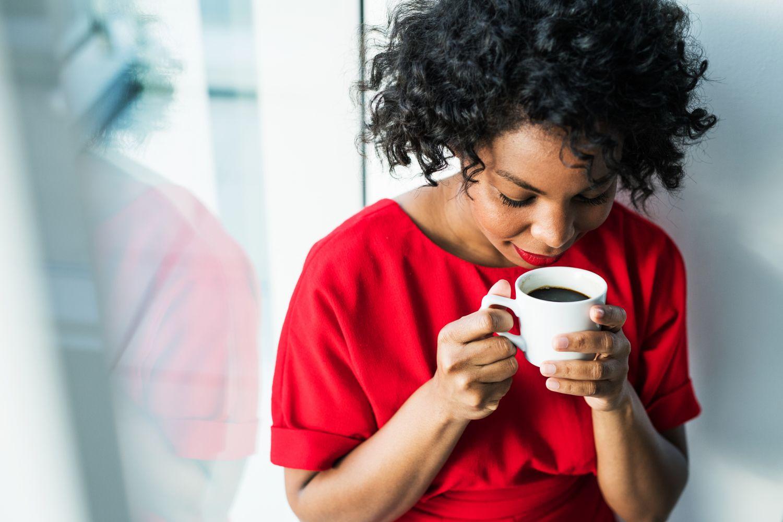 Eine Frau steht am Fenster und trinkt eine Tasse Kaffee. Thema: Kaffee am Arbeitsplatz