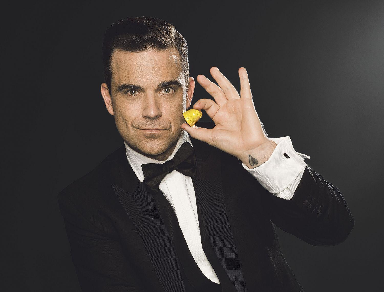 Der Sänger Robbie Williams hält eine Kaffeekapsel zwischen den Fingern
